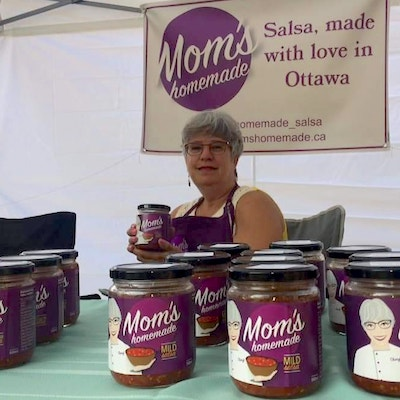 IMAGE: Cheryl shows off some of the Mom's Homemade at the Beechwood Market in Ottawa.